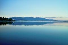 在平实水的看法在水坝Liptovska玛拉有Havranok教会的背景 在Liptov的水库 免版税库存照片