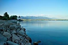 在平实水的看法在水坝Liptovska玛拉有Havranok教会的背景 免版税库存照片
