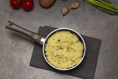 在平底深锅的土豆泥在黑暗的背景,顶视图 可口热的土豆泥用黄油和切得很细的新鲜的草本 免版税图库摄影
