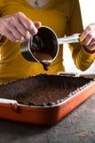 在平底深锅的热巧克力,在烘烤盘的面团 库存图片
