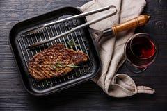 在平底锅和红葡萄酒的烤牛排 库存图片