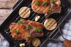 在平底锅格栅特写镜头的烤猪肉牛排,水平的顶视图 免版税库存照片