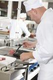 在平底锅的专业厨师油炸物牛排在厨房 免版税图库摄影