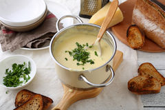 在平底锅的乳酪汤在桌上 库存照片