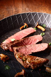 在平底锅的切的烤牛排 免版税库存照片