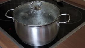 在平底锅的开水有在归纳玻璃陶瓷现代火炉厨师上面的一个闭合的盒盖的 股票录像