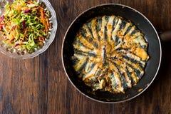 在平底锅的新鲜的油煎的沙丁鱼用木表面上的沙拉 免版税库存照片