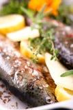 在平底锅的新鲜的鳟鱼用黄油用柠檬和麝香草 免版税库存图片