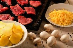在平底锅的未加工的使有大理石花纹的牛排 免版税库存图片