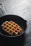 在平底锅的比利时华夫饼干在黑暗的石背景垂直 库存照片