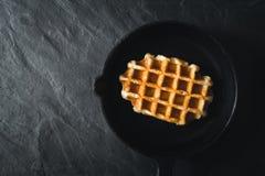 在平底锅的比利时华夫饼干在黑暗的石背景顶视图 库存图片