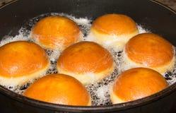 在平底锅的烘烤油炸圈饼 免版税图库摄影