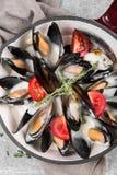在平底锅的煮熟的淡菜在餐巾服务装饰用蕃茄和麝香草 在白葡萄酒调味汁的蒸的淡菜 免版税库存图片