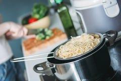 在平底锅的面团意粉在烹调妇女背景  免版税库存照片