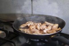 在平底锅的鸡在火炉 免版税库存图片