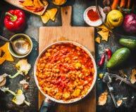 在平底锅的素食辣豆汤盘在木切板用烹调在黑暗的厨房tabl的香料和菜成份 免版税库存照片
