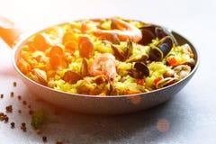 在平底锅米,豌豆,虾,淡菜,在浅灰色的具体背景的乌贼的传统西班牙海鲜肉菜饭 顶层 图库摄影