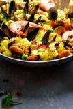 在平底锅米,豌豆,虾,淡菜,在浅灰色的具体背景的乌贼的传统西班牙海鲜肉菜饭 顶层 免版税库存照片