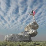 在平衡安排的岩石顶部的体操运动员 免版税库存图片