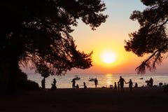 在平衡的海滩休息的人民 日落 库存图片