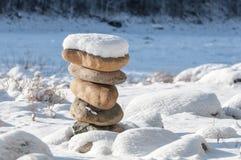 在平衡的石头在冬天沿岸航行在雪下 库存图片