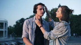 在平衡软的阳光的爱恋的年轻夫妇 女孩在她的男朋友` s头和亲吻投入她的耳机他 公园 股票录像
