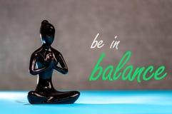 在平衡-瑜伽妇女小雕象生活方式实践思考和能量瑜伽 健康的概念 库存照片