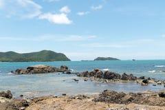 在平静海滩岩石海岸线的看法  免版税库存照片