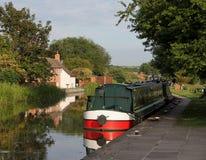在平静的场面的运河狭窄的小船 库存照片