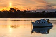 在平静的港口的小船日落的 库存照片