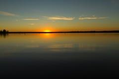 在平静的湖的橙色太阳 免版税图库摄影