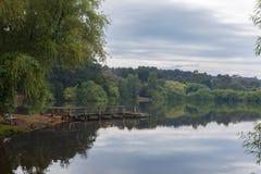 在平静的Daylesford湖的小跳船在春雨以后 免版税库存照片