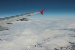 在平面翼阴暗和积雪的山下 免版税图库摄影