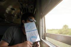 在年轻亚裔行家的面孔的选择聚焦有地图的在火车 浅深度的域 阳光作用 库存照片