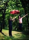 在年轻人之下的夫妇伞 库存照片