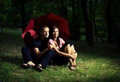 在年轻人之下的夫妇伞 库存图片