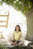在年轻人之下的女孩坐的结构树 库存照片