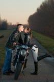 在年轻人的夫妇亲吻的摩托车 库存图片