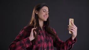 在年轻和美丽的白种人长发女孩档案的画象谈话在videochat使用在黑色的智能手机 股票录像