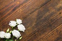 在年迈的木背景安排的白花 库存照片