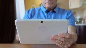 在年迈的男性手的白色片剂个人计算机 免版税库存照片