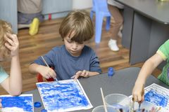 在幼儿园的孩子绘画 免版税库存图片