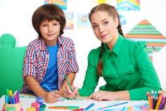 在幼儿园的小男孩和老师图画 免版税库存照片