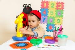 在幼儿园的非裔美国人的黑男孩图画在桌上在幼儿园 免版税库存照片