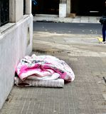 在幼稚桃红色盖子下的无家可归者 免版税图库摄影