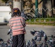 在广场Murillo -拉巴斯,玻利维亚的男孩哺养的pidgeons 免版税库存照片