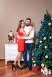 在庆祝圣诞节的爱的年轻愉快的夫妇 图库摄影