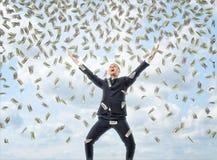 在庆祝姿势的愉快的商人与金钱装载在天空中 免版税库存图片