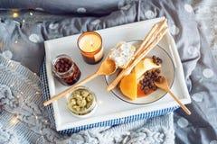 在床、一个盘子用乳酪, grissini、果酱从年轻冷杉球果和一个蜡烛用早餐 圣诞节森林上了凸边早晨多雪的线索宽冬天 蜜月 在美丽的鸟云彩之上颜色及早飞行金子早晨本质宜人的平静的反映上升海运一些星期日 免版税库存照片
