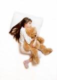 在床上和拥抱玩具熊的射击逗人喜爱的女孩 免版税库存照片